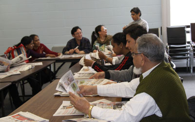 teacher and adult students looking at newspapers