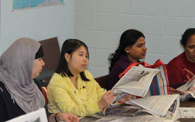 adult students looking at newspapers