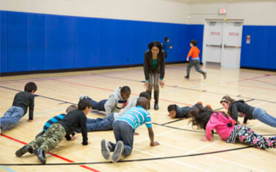 Teacher leading kids in push up exercise